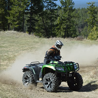 A guy on a green ATV going fast around a corner.