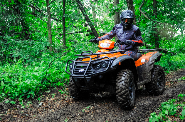 A group of riders coming up a trail on the new Argo four wheelers.