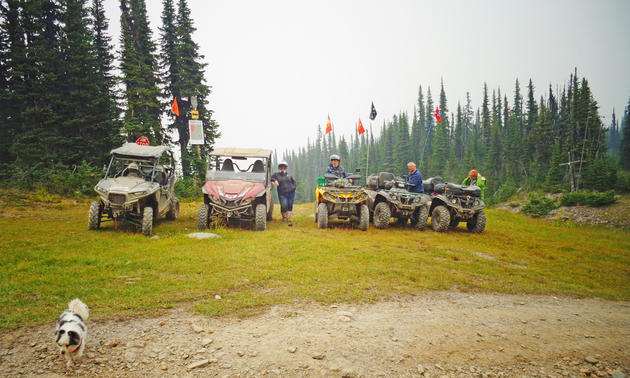 Shown are five ATVs and their riders parked in a field for a break.