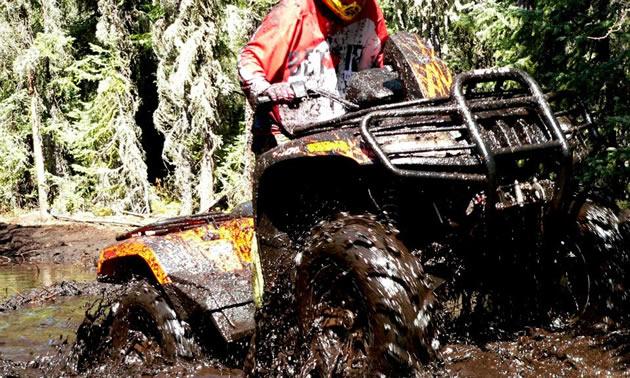 An ATV tearing through deep mud.