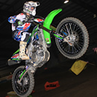 A young man going over a jump on a neon green dirt bike.