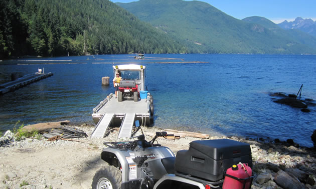 Offloading ATVs onto the shore from a barge.