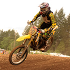 A young man landing a yellow dirt bike over a jump.