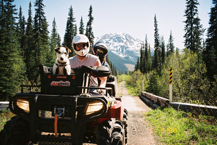 A man and his dog sit and pose for the camera on an ATV on a trail through the forest and mountains
