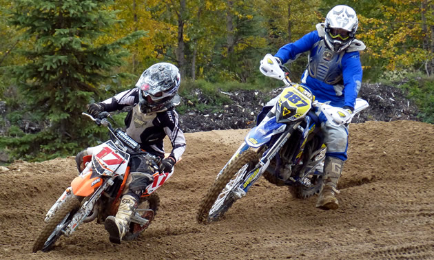 Two motorcyclists race around a dirt track in the woods.