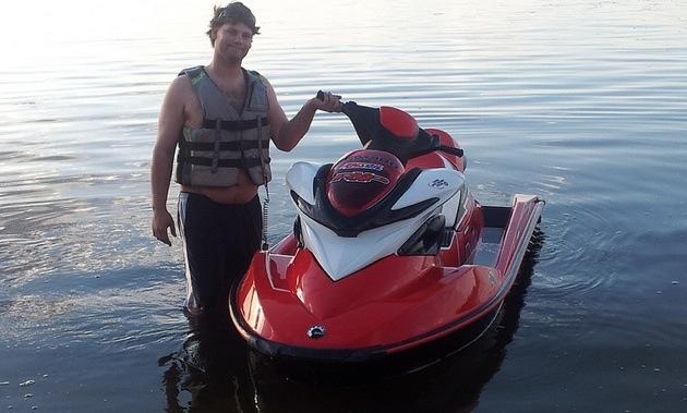 A man standing knee deep in water next a Personal Watercraft.