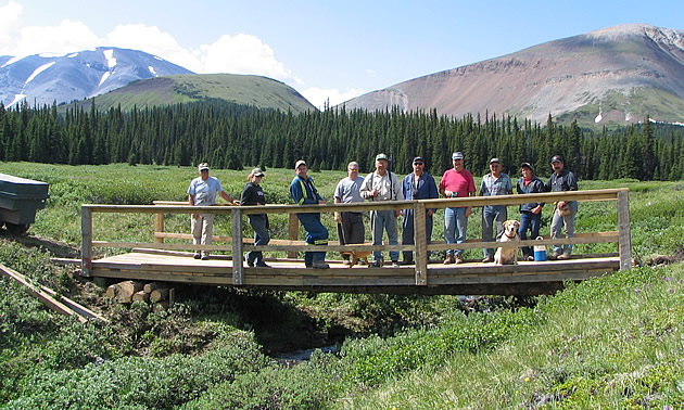 A group of people standing on a bridge.