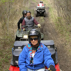 A lady in a blue jacket riding a red quad is in front of two other ATVs riding on a grassy trail.