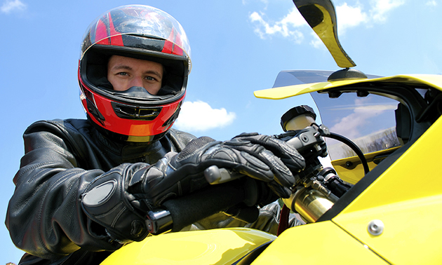 A man wearing a red and black helmet sitting on a yellow bike with the sky in the background.