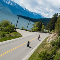 Two motorcyclists travelling down a road along a lake.