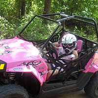 A youth riding a RZR side by side.