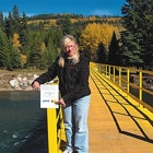 Woman standing on a wooden bridge over a river in the backcountry