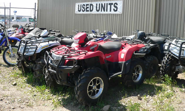 Photo of a red ATV sitting underneath a sign that says Used Units.