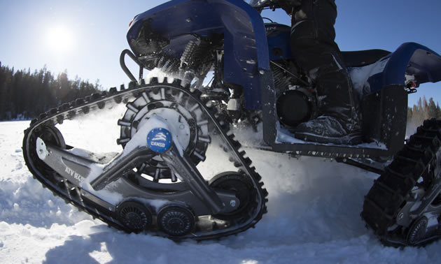 A smaller ATV with a track system in the snow.