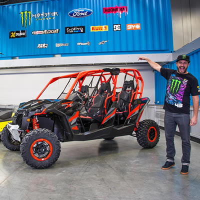 Ken Block standing beside his red and black Can-Am side-by-side.