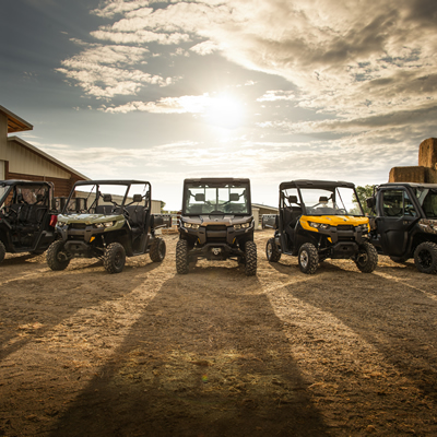 Five of Can-Am's new Defender utility side-by-sides lined up in a farmyard.