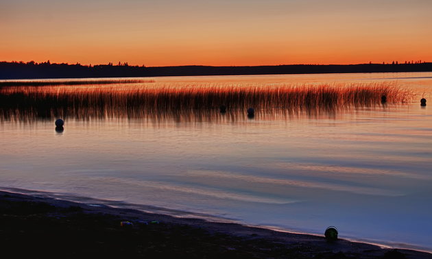 Sunset colours reflect on a calm lake in Duck Mountain Provincial Park.