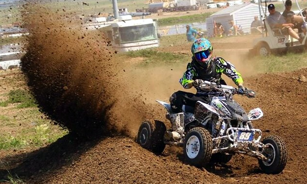 A roost of dirt as an ATV racer comes around the corner.