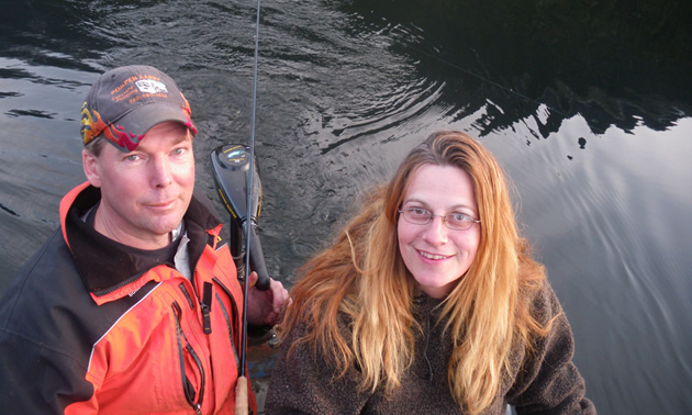 Photo of a man in a ball cap and a woman with light brown hair smiling at the camera while they are fishing on a boat.