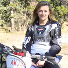 Photo of a girl with long brown hair in her mid twenties sitting on a blue dirt bike.