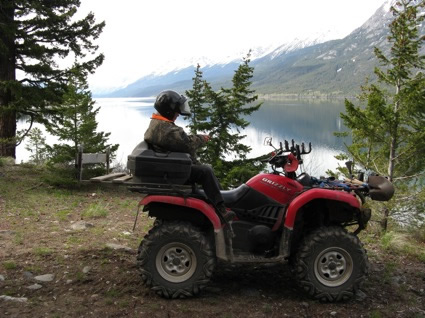 An ATVer sits on the back of a quad in front of a mountain lake