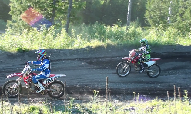 Photo of two people riding dirt bikes on a dirt track.