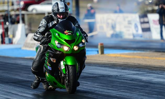 Chris Klassen drag racing his motorcycle down the asphalt.