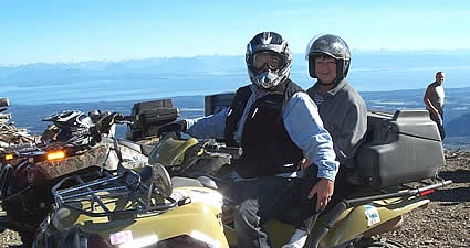 Photo of two people on a quad on a mountain