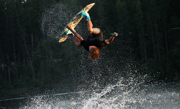 Colden Thompson is upside down above the water as he performs a melon 360.