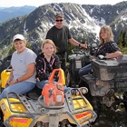People sitting on ATVs at a mountain location