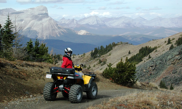 Riders come from near and far to experience the amazing beauty of Southern Alberta's backcountry. Shown is an ATVer parked with the Rocky Mountains in the background.