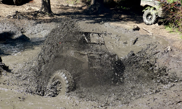 A SxS spinning up mud in a giant puddle.