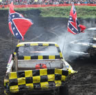 A yellow truck, decked out with confederate flags, smashes into a black truck in front of a large crowd.