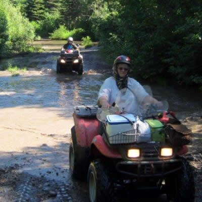 A woman on an ATV riding through a mud puddle.