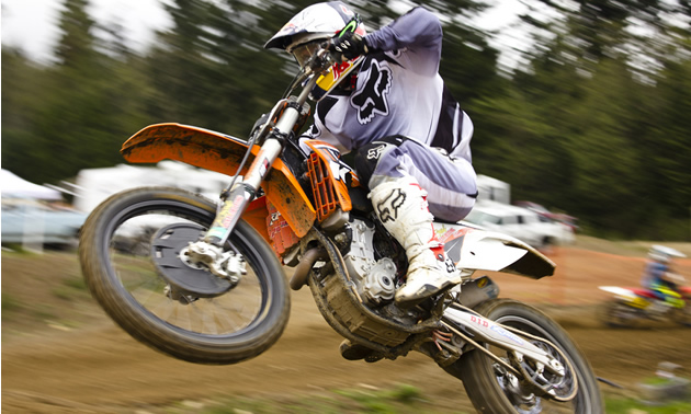 A guy popping a wheelie on a dirt bike.
