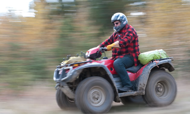Man riding an ATV down dirt road.