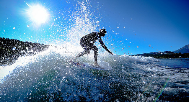 Gabrielle Hockley wake surfing, with the sun's rays shining over the wave behind her.