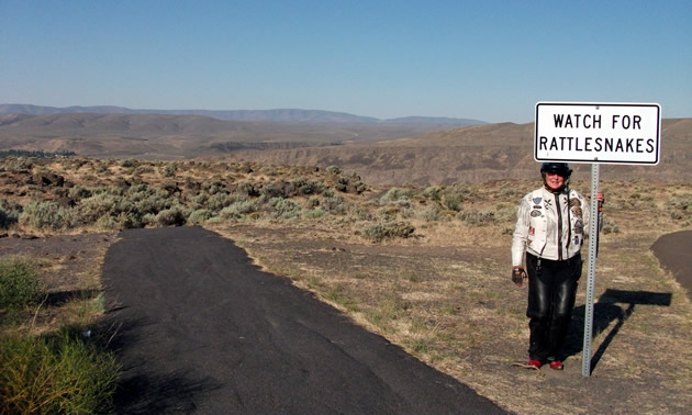Gina standing underneath a sign that says, Watch for Rattlesnakes.
