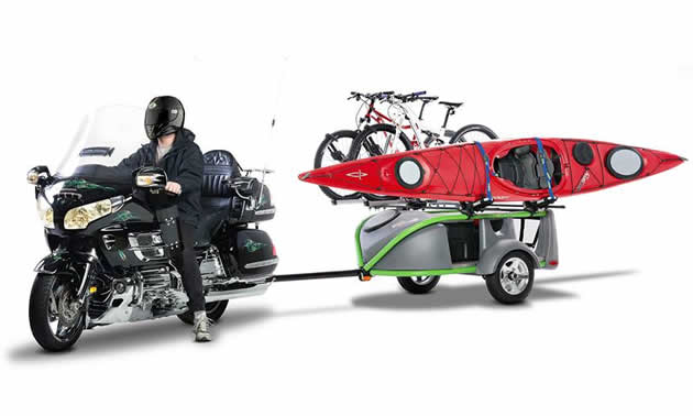A black cruiser motorcycle towing a trailer with bikes and a kayak on it.