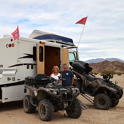 A man and woman standing by their modified toy hauler with ATVs.