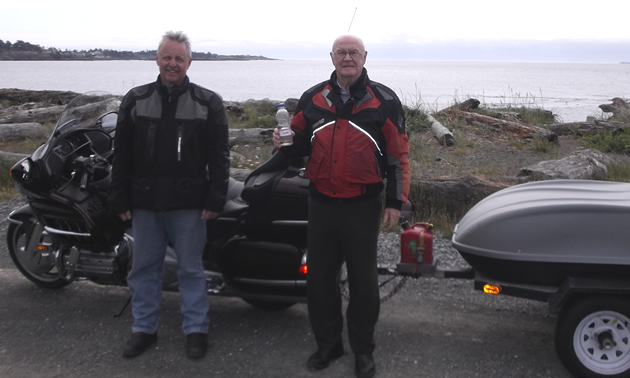 Photo of an older gentleman and a middle-aged man standing in front of a BMW motorcycle with a trailer attached to it. The rig is parked beside the ocean.