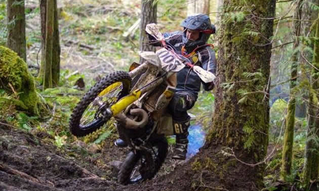A dirt biker ascends a hill in the woods by doing a wheelie.