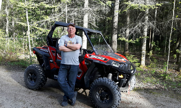 An older gentleman standing beside a red quad in the forest.