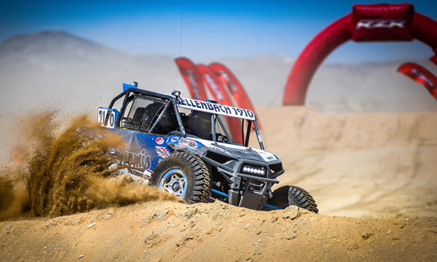A Hellenbach Racing UTV is racing through desert sand.