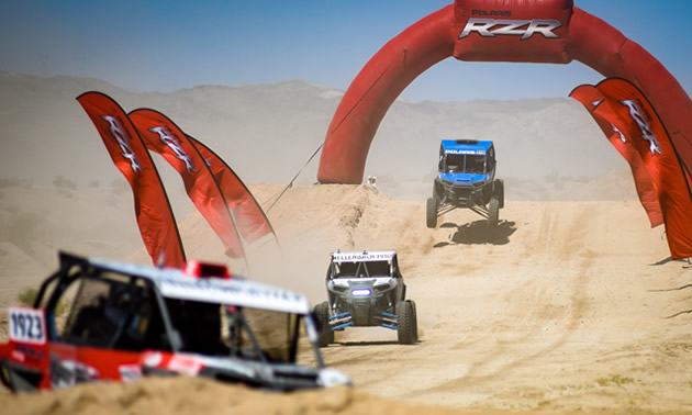 Pictured are several UTVs racing in the desert.