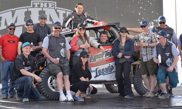 The team is posed next to one of its UTVs at the Mint 400.