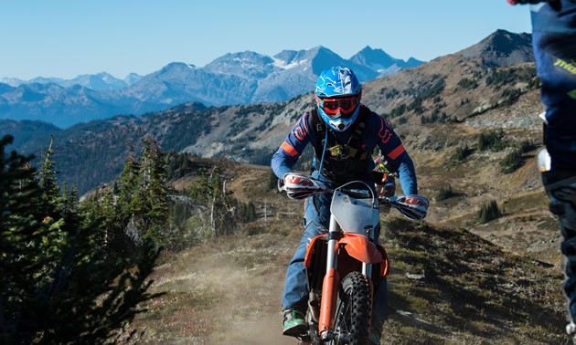 A shot of Jason Ribi riding toward the camera and behind him is mountainous terrain.