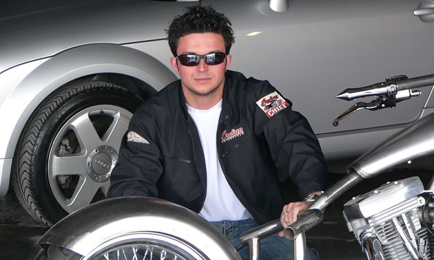 Photo of a young man with black hair kneeling between a car and a custom chopper.
