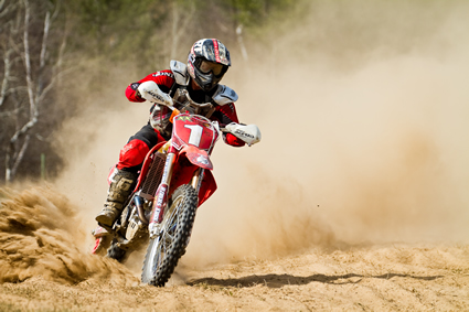 A guy riding around a turn on a dirt bike with dust billowing