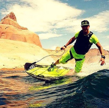 A man riding a JetSurf on a lake that is in the desert.